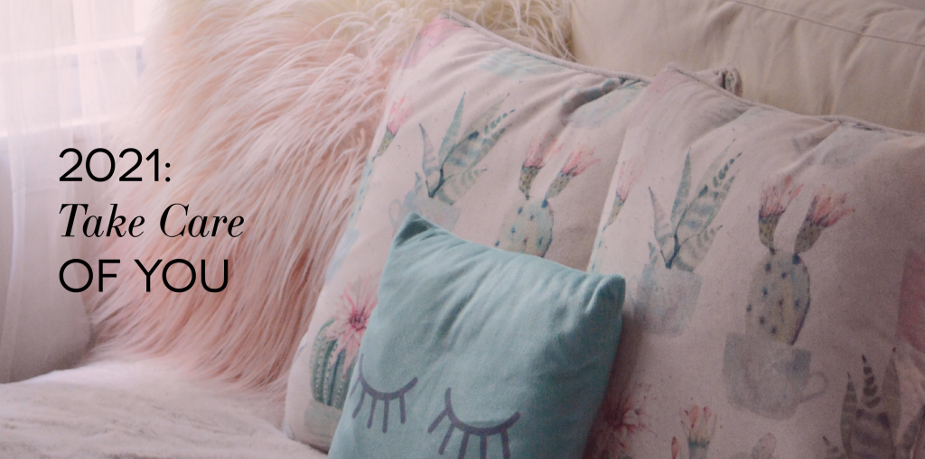 "Image of pink hued pillows on a bed. Some have fur, some depict cacti, and one has a drawing of eyelashes. The text on the image reads ""2021: Take Care of You"""
